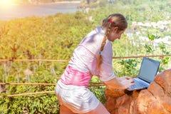 En ung kvinna arbetar med en bärbar dator på överkanten av berget med sikt på den sandiga tropiska stranden arbete och resande arkivfoton