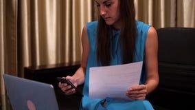 En ung kvinna arbetar med hennes bärbar dator på ett svart skrivbord med legitimationshandlingar 4K stock video