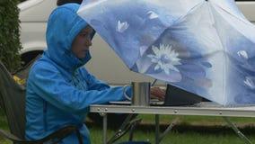 En ung kvinna arbetar på bärbara datorn under det blåa paraplyet under regn stock video