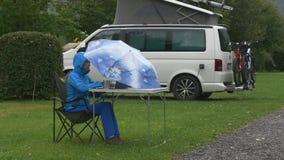 En ung kvinna arbetar på compiter på picknicktabellen under paraplyet under regn arkivfilmer