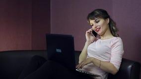 En ung kvinna arbetar på en dator, medan sitta på en liten soffa stock video
