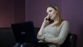 En ung kvinna arbetar på en dator, medan sitta på en liten soffa arkivfilmer