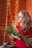 En ung kvinna dekorerar ett hus för jul och ett nytt år royaltyfri bild