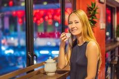 En ung kvinna dricker kinesiskt te på en bakgrund av röda kinesiska lyktor i heder av det kinesiska nya året royaltyfria foton
