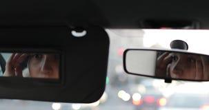 En ung kvinna eller en flicka ser i spegeln på henne sammanträde i bilen stock video