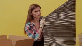 En ung kvinna flyttar och väljer upp tapeten för reparation arkivfilmer