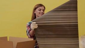 En ung kvinna flyttar och väljer upp tapeten för reparation lager videofilmer