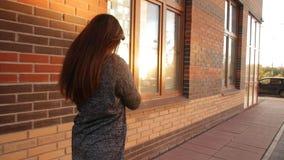 En ung kvinna går gatorna av staden på solnedgången stock video