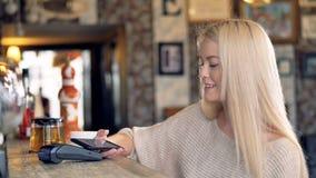 En ung kvinna gör en contactless betalning och vinkar till någon stock video