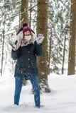 En ung kvinna har gyckel i winterly en skog royaltyfri bild