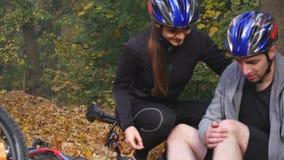 En ung kvinna hjälper en man som har stupat från en cykel stock video