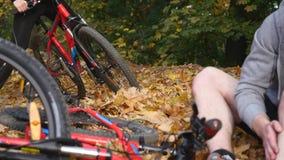 En ung kvinna hjälper en man som har stupat från en cykel lager videofilmer