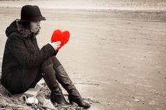 En ung kvinna i en hatt och ett lag sitter på kusten av fjärden på ett fisknät med en flott hjärta i hennes händer, sepia, kopier Arkivbild