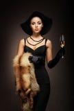 En ung kvinna i en klänning som rymmer ett exponeringsglas av champagne Royaltyfri Fotografi