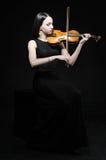En ung kvinna i en svart klänning med en fiol Royaltyfri Foto