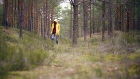 En ung kvinna i ett ljust gult omslag som går på den regniga skogen arkivfilmer