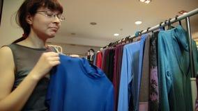 En ung kvinna i exponeringsglas väljer kläder som hänger på hängare i ett lager stock video