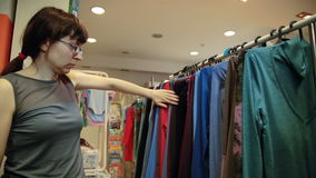 En ung kvinna i exponeringsglas väljer kläder som hänger på hängare i ett lager arkivfilmer