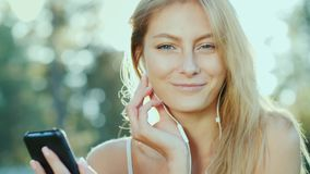 En ung kvinna i hörlurar lyssnar till musik, använder en smartphone Solen exponerar beautifully hennes hår royaltyfri bild