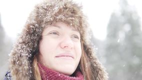 En ung kvinna i en pälshatt med earflaps ser dreamily himlen stock video