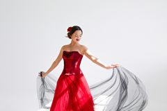 En ung kvinna i en röd klänning dansar Latin utformar Isolat på vit royaltyfria bilder