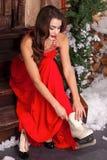 En ung kvinna i röd klänning för vinter på en farstubro som dekoreras med julpynt som sätter på skridskor som ner ser arkivfoto