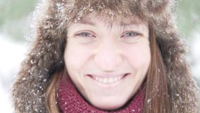En ung kvinna i en varm vinterhatt tycker om den fallande snön arkivfilmer