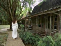 En ung kvinna i en vit klänning som går ner banan till huset I bakgrunden finns det en tropisk skog och mycket gräsplan stock video