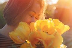 En ung kvinna inhalerar doften av vårblommor, gula tulpan Begrepp av allergin close upp royaltyfri foto