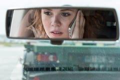 En ung kvinna kör en bil och talar på telefonen arkivfoto