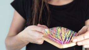 En ung kvinna kammar sluten av hennes hår lager videofilmer