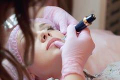 En ung kvinna ligger och får ett smink av hennes ögonbryn i en skönhetsalong Bruket av permanent makeup på ögonbrynen Förlagen w Arkivfoton