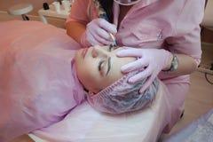 En ung kvinna ligger och får ett smink av hennes ögonbryn i en skönhetsalong Bruket av permanent makeup på ögonbrynen Förlagen w Fotografering för Bildbyråer