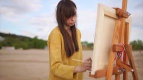 En ung kvinna målar en målarpensel med en stilleben på en staffli, på den öppna luften lager videofilmer