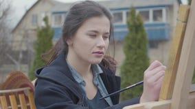 En ung kvinna målar en målning på en kanfas som står bak en staffli, i ett atmosfäriskt seminarium i trädgården arkivfilmer