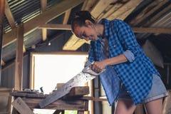 En ung kvinna med en bågfil i hennes bräden för såga för händer i det hem- seminariet arkivbild