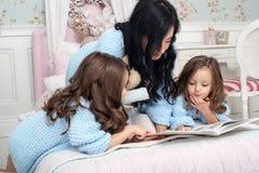 En ung kvinna med barnblått sticker koftan i sängen nära julkransen royaltyfri foto