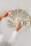 En ung kvinna med dollar i hennes händer som isoleras på vit Royaltyfria Bilder