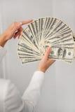 En ung kvinna med dollar i hennes händer som isoleras på vit Fotografering för Bildbyråer