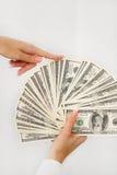 En ung kvinna med dollar i hennes händer som isoleras på vit Royaltyfri Fotografi