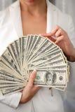En ung kvinna med dollar i hennes händer som isoleras på vit Arkivfoton