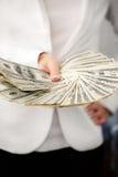 En ung kvinna med dollar i hennes händer som isoleras på vit Royaltyfria Foton
