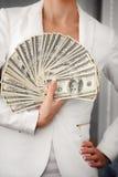 En ung kvinna med dollar i hennes händer som isoleras på vit Arkivfoto