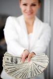En ung kvinna med dollar i hennes händer som isoleras på vit Royaltyfri Foto