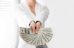 En ung kvinna med dollar i hennes händer som isoleras på vit Arkivbild