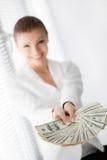 En ung kvinna med dollar i hennes händer som isoleras på vit Arkivbilder