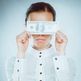 En ung kvinna med dollar i hennes händer som isoleras på vit bakgrund Arkivbild