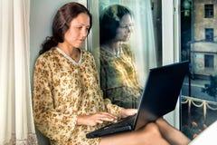 Den unga kvinnan på fönstret med en bärbar dator Royaltyfria Bilder
