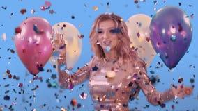 En ung kvinna med ett exponeringsglas i hennes hand, i en guld- klänning lanserar confit Hon ler och tycker om ferien Bredvid stock video