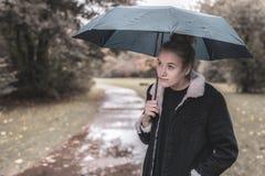 En ung kvinna med ett paraply väntar på bättre väder arkivbild